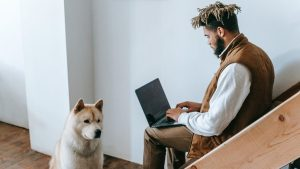 serious ethnic man working distantly on laptop sitting on staircase near calm dog